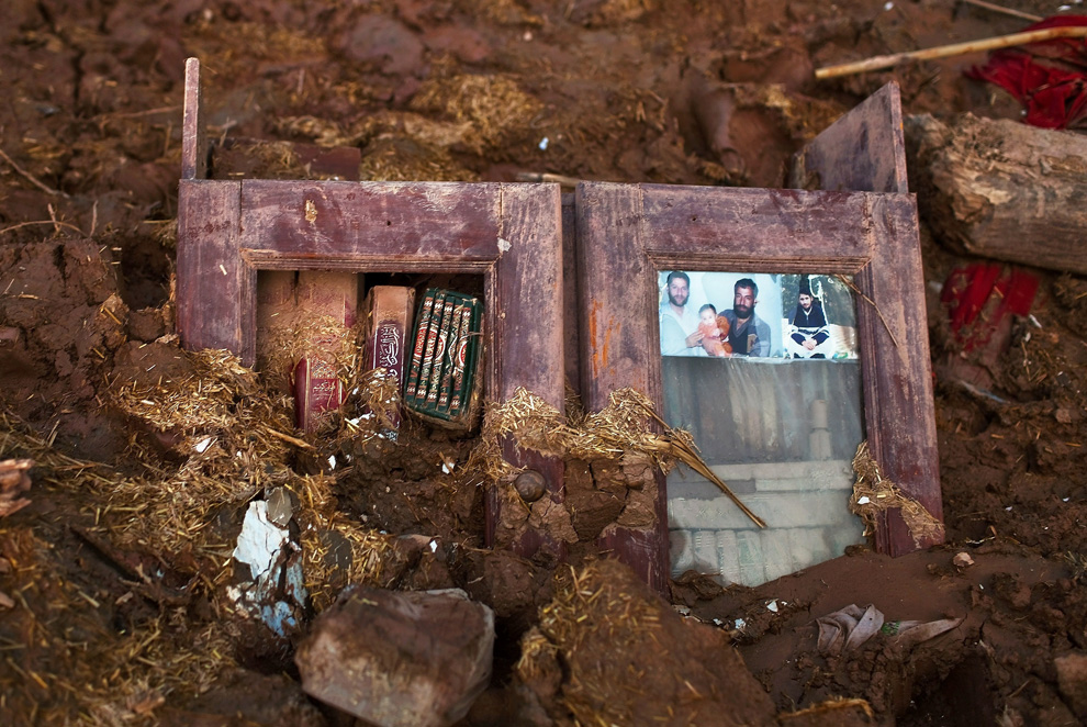 A family portrait is seen, attached to a bookcase buried in mud on August 4, 2010 in Pabbi, Pakistan. (Daniel Berehulak/Getty Images)