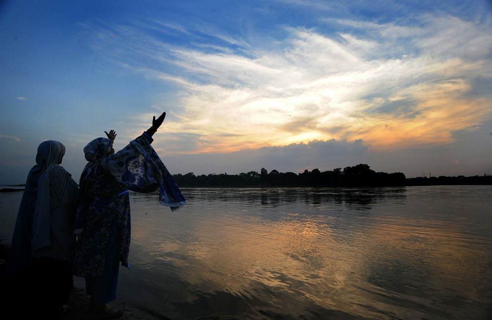 Pakistani women pray at sunset by the Ravi river in Lahore on August 2, 2010. (Arif Ali/AFP/Getty Images)