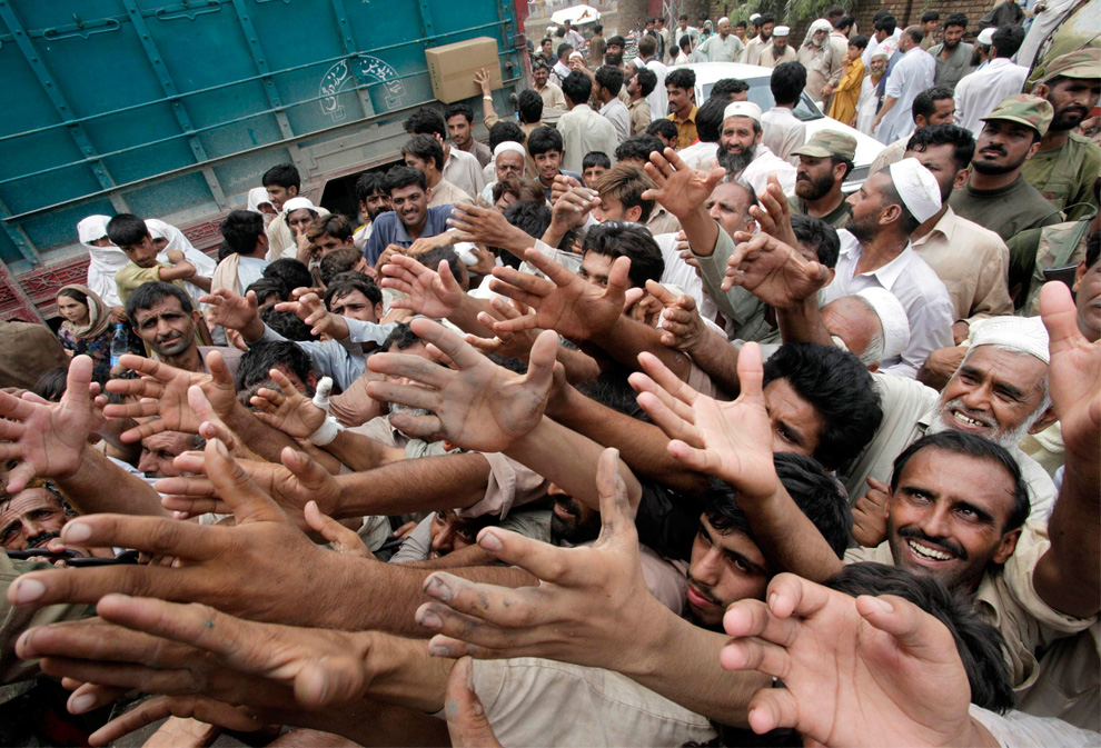 Flood-affected people jostle for food relief in Nowshera in northwest Pakistan on Friday, Aug. 6, 2010. (AP Photo/Mohammad Sajjad)