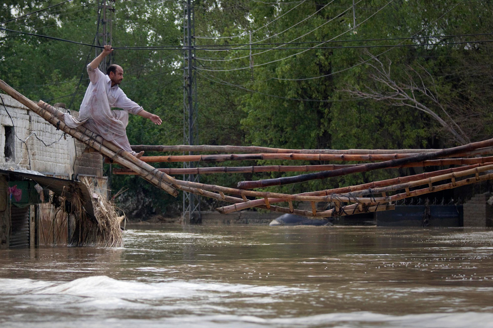 A man tries to cross a makeshift bridge to escape his flooded home in Nowshera, Pakistan on July 31, 2010. (REUTERS/Adrees Latif)