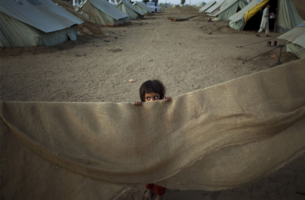 A young girl peers over part of a makeshift tent in Swabi [AP Image]