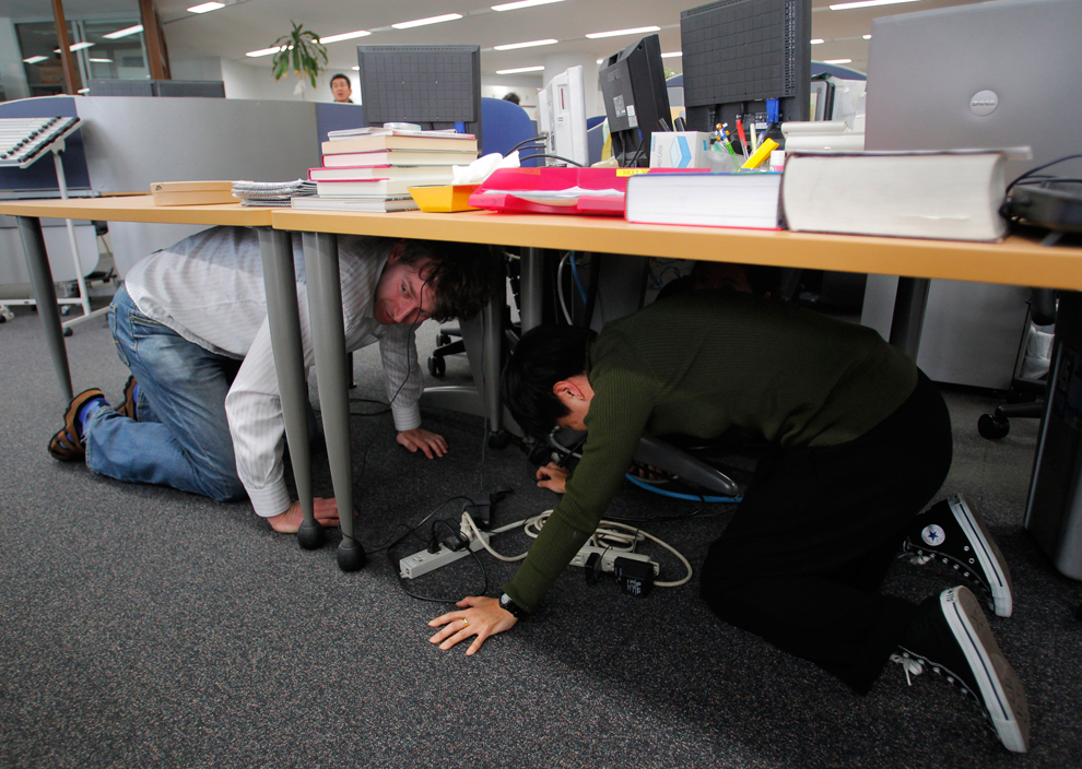 Reporters at the Associated Press Tokyo Bureau in Tokyo take shelter under a table while a strong earthquake strikes eastern Japan. (Itsuo Inouye/Assoctiated Press)