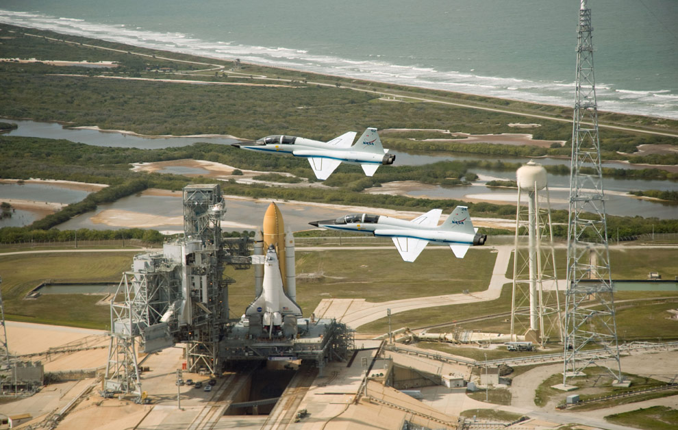 Two NASA T-38 jet trainer aircraft fly over the Space Shuttle Endeavour on Pad 39B at the Kennedy Space Center. After Atlantis leaves Pad A (out of frame), Endeavour will be moved from Pad B to Pad A to support the STS-127 mission. Currently, Endeavour is being prepared as a backup vehicle for Atlantis, and it will be designated STS-400 if in the unlikely event its needed for a rescue flight. The two pictured aircraft were piloted by Jack Nickel (in jet with tail number 62, top) and Charles Justiz (in jet with tail number 24). (NASA)