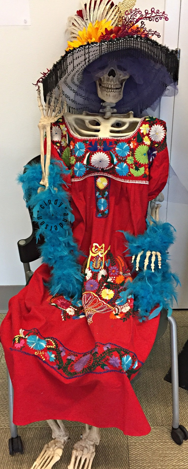 A skeleton dressed with a wildly decorated hat, teal feathered scarf and a red dress with multi-colored embellishments.