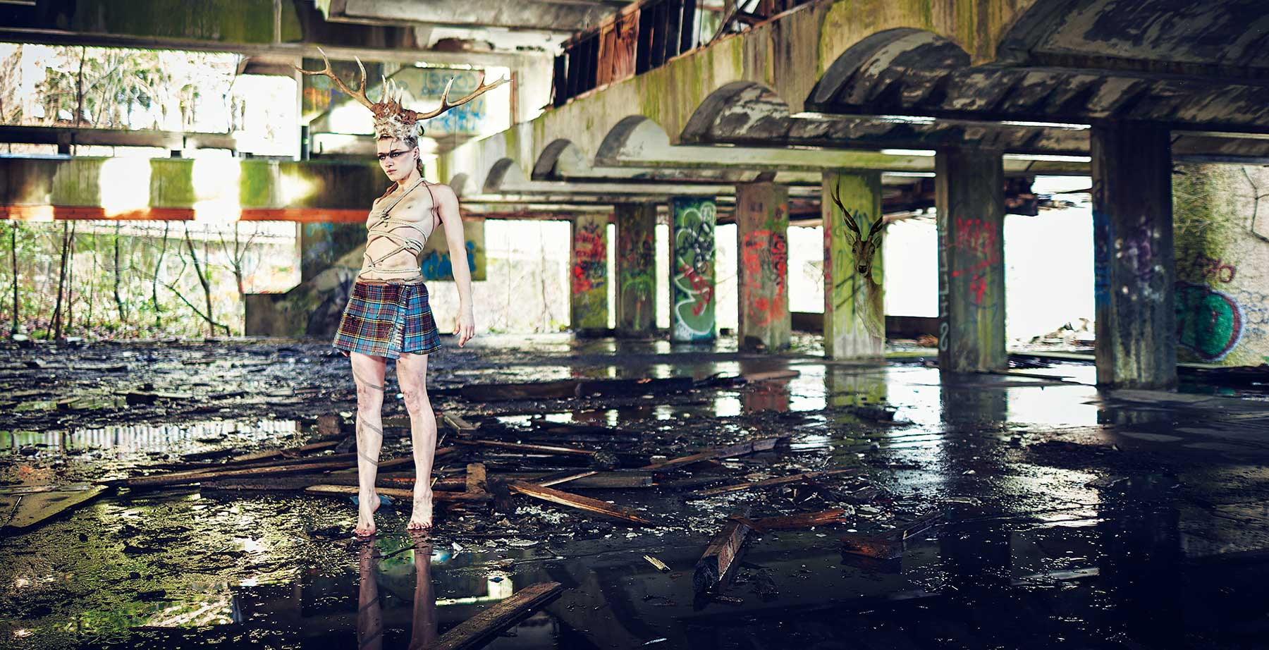 warrior sister in an abandoned building wearing only a kilt and stag antlers on her head