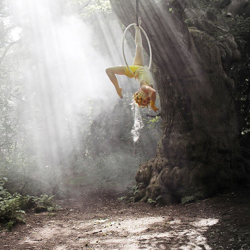 Kate George hangs from a trapeze hoop in a forest