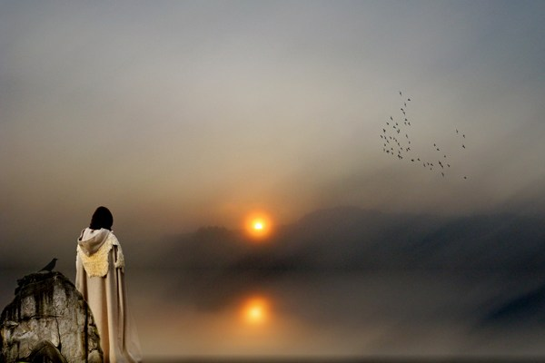 Photo of man with robe looking at setting sun