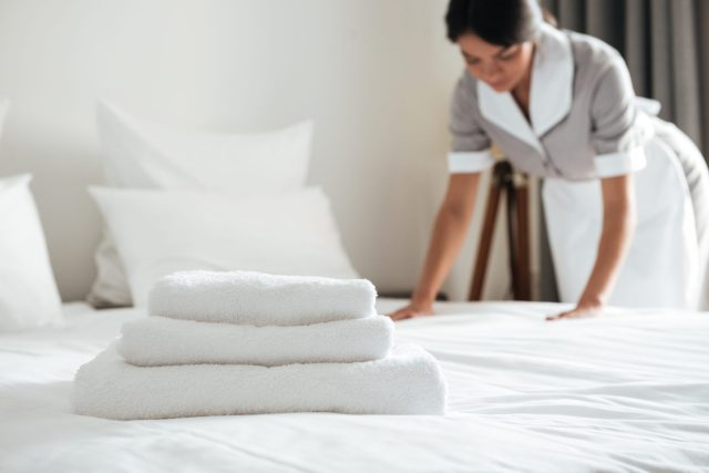 Young hotel maid setting up pillow on bed