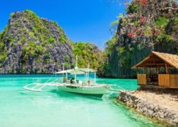 The picture highlights a beautiful view of a beach in the Philippines with a small motor boat that is about to dock at a small port. In the background there is a lush forest that acts as a contrast to the transparent sea.