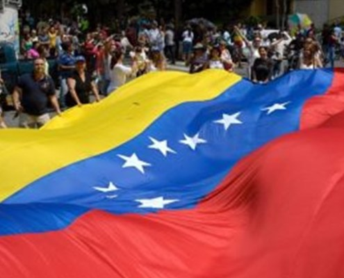 The picture highlights a large Venezuelan flag held in the hands of a large crowd in the middle of the road.