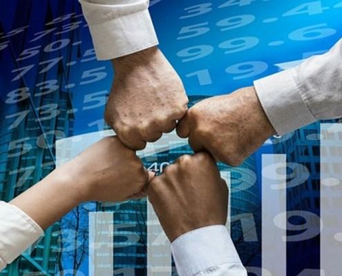 L'immagine evidenzia quattro braccia tese con le mani strette a pugno chiuso che convergono al centro della fotografia che ha come sfondo delle quotazioni elettroniche.