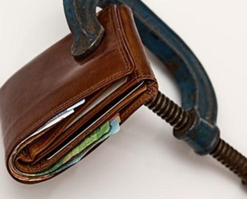L'immagine evidenzia un portafoglio schiacciato in una morsa a rappresentare le regole ed i vincoli dell'U.E. nell'attuale crisi finanziaria italiana.