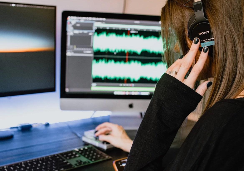 Mulher com fone de ouvido em frente a um computador cuja tela mostra ondas sonoras