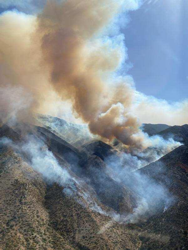 Aerial photo shows dark smoke rising from active fire in hilly terrain (taken 5/9 AM)