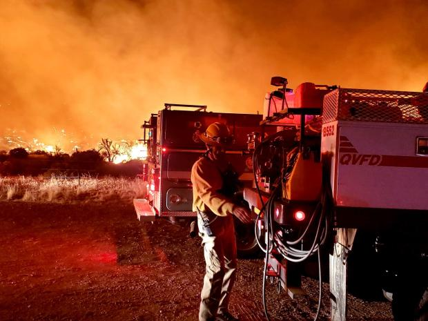 Glow from the Telegraph Fire falls on firefighting resources as they work through the night