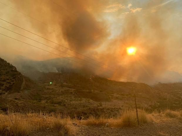 The morning sun shines through thick smoke. Flames are visible along the rolling hillsides in the distance.