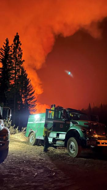 Image of Forest Service engines with red night sky in background.