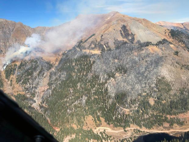A mountain side with smoke rises in places is shown. The South Fork Mineral Creek Road is visible at the bottom.