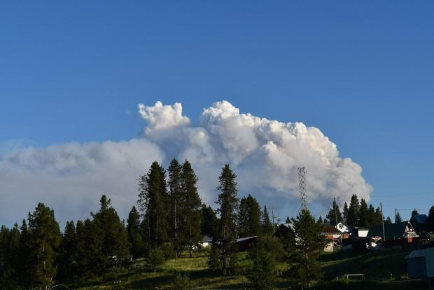 Smoke rises from the Dixie fire with buildings from a nearby town in the foreground.