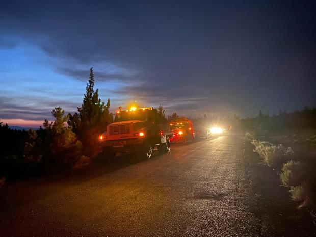 Engines are lined up along a roadside as headlights shine towards the camera. The sky is darkening behind them.