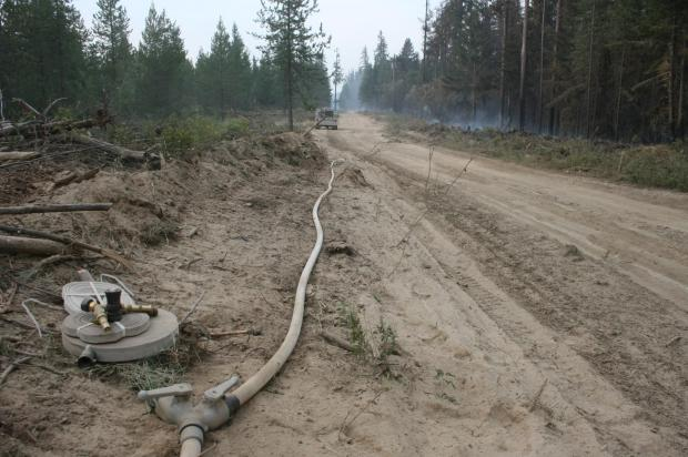 A fire engine watches a smoky forest, a  hoseline runs down a road