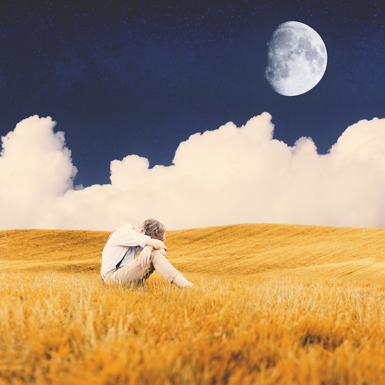 Boy sits curled up in field beneath moon and clouds.