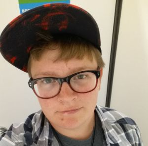 a white male with a red and black hat and red and black rimmed glasses looks up at the camera with a small smile