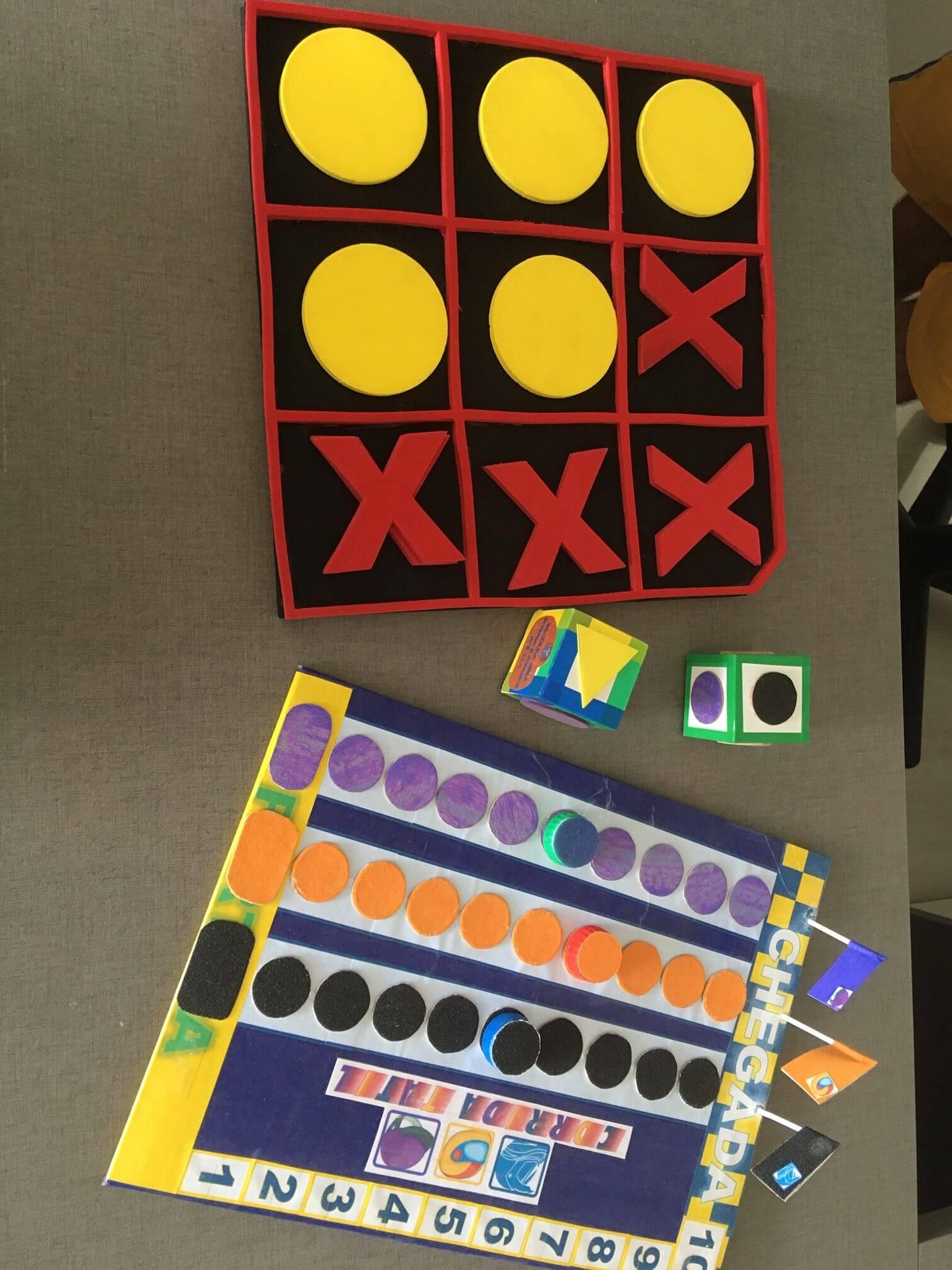 Imagem ilustrativa mostrando dois jogos adaptados para deficientes visuais e dois dados com texturas para jogos inclusivos.