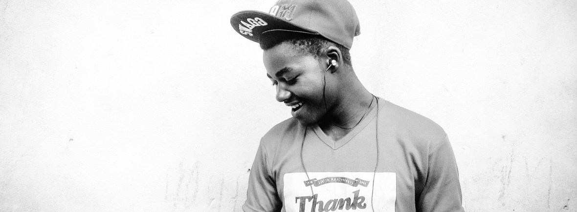 "Smiling male teen with brown skin wearing earbuds, a cap, and a t-shirt that says ""thank you."""