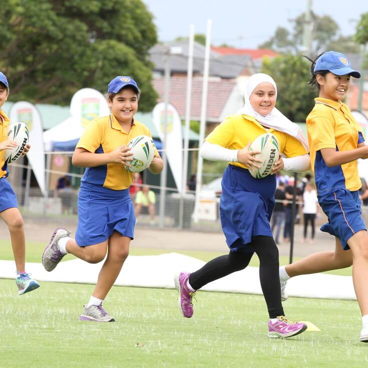 Girl in head scarf playing rugby league with other girls.