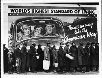 Famous image of African American flood victims lined up to get food & clothing fr. Red Cross relief station in front of billboard ironically extolling WORLD'S HIGHEST STANDARD OF LIVING/ THERE'S NO WAY LIKE THE AMERICAN WAY. Louisville, KY, 1937