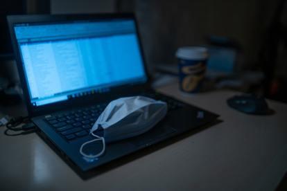 Computador portátil durante teletrabalho e máscara de COVID-19