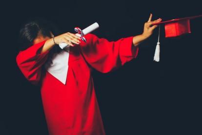 Mulher jovem licenciada com traje da cerimónia de graduação de curso de ensino superior numa universidade. Portugal tem 40% de jovens licenciados
