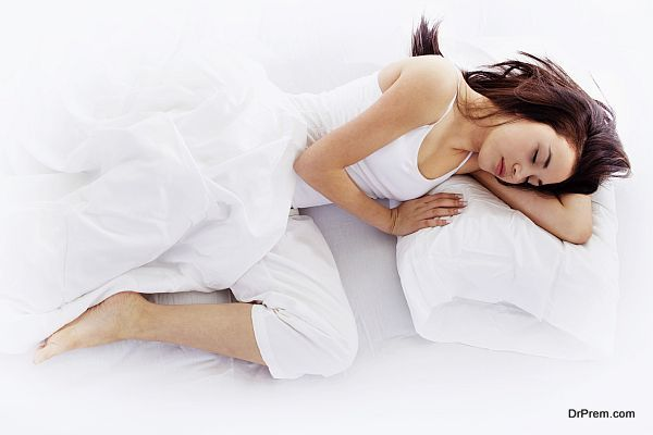 Young woman sleeping on white bed