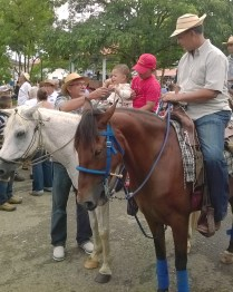 This little guy's abuelo put him up on a horse.