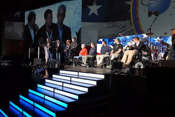 Awardees on stage in wheelchairs