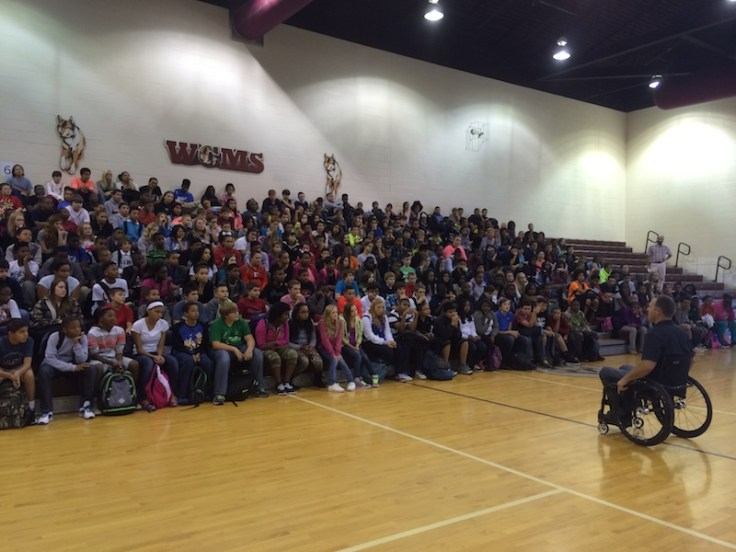 Gary Linfoot talking to student audience in gym