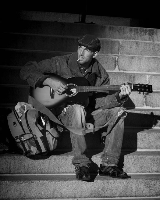 Homeless-man on steps with guitar