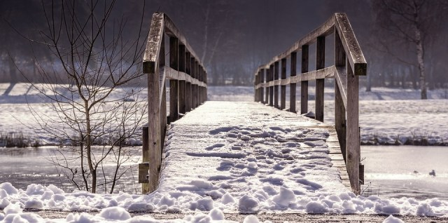 Old snow covered Bridge over creek