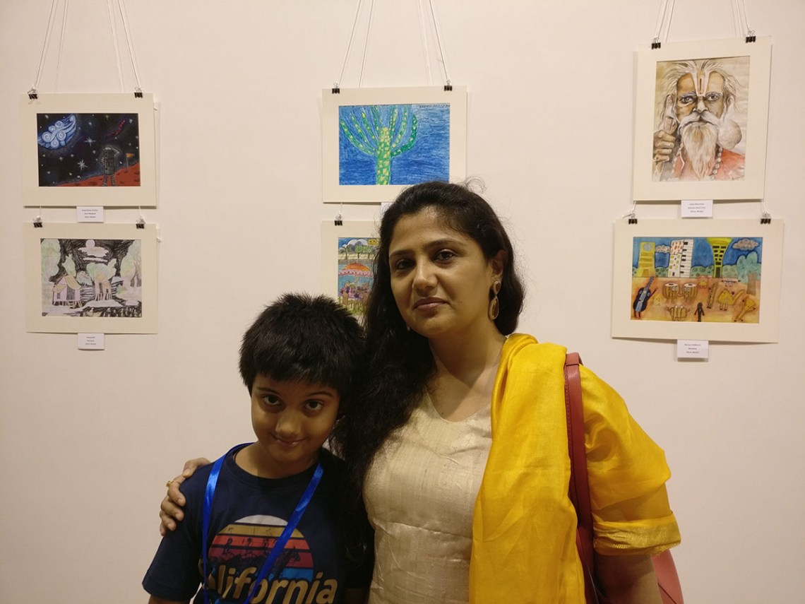 Aarav Kanekar with his mother Vrushali Kanekar at Khula Aasmaan art exhibition of medal winning artworks. Aarav's video is part of videos of medal winning children.