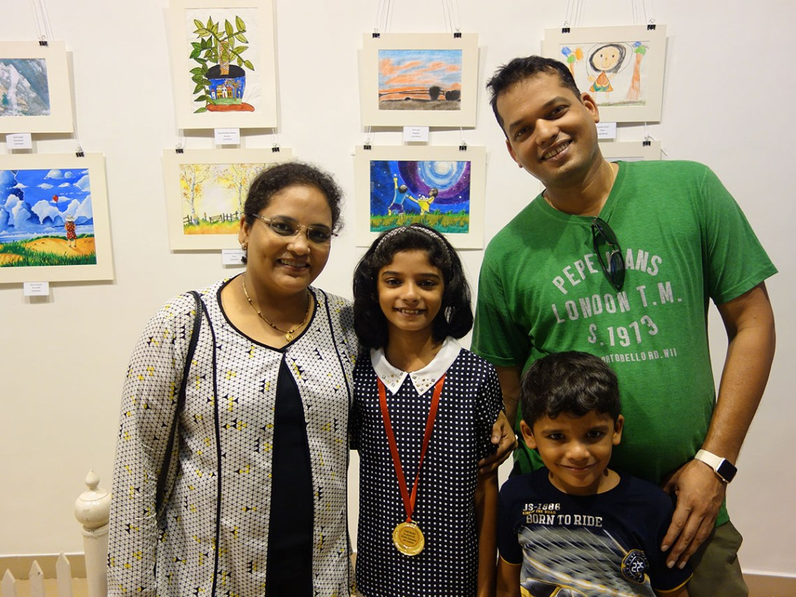 Riya Bhat with her family in front of her painting at Khula Aasmaan art exhibition at Mumbai - October 2017. Riya's video is part of videos of medal winning children.