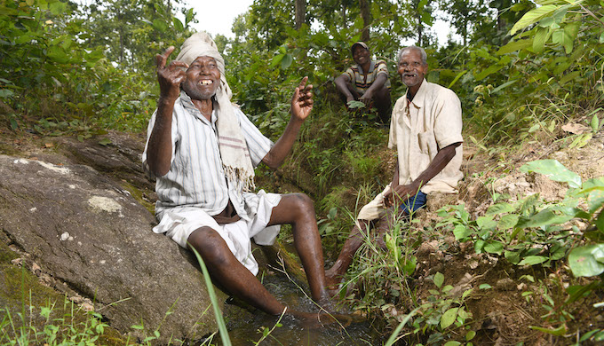 The jovial pani baba with his fellow villagers in a small water stream in the woodland near Gaighat dam. This rivulet is used to distribute water from the reservoir