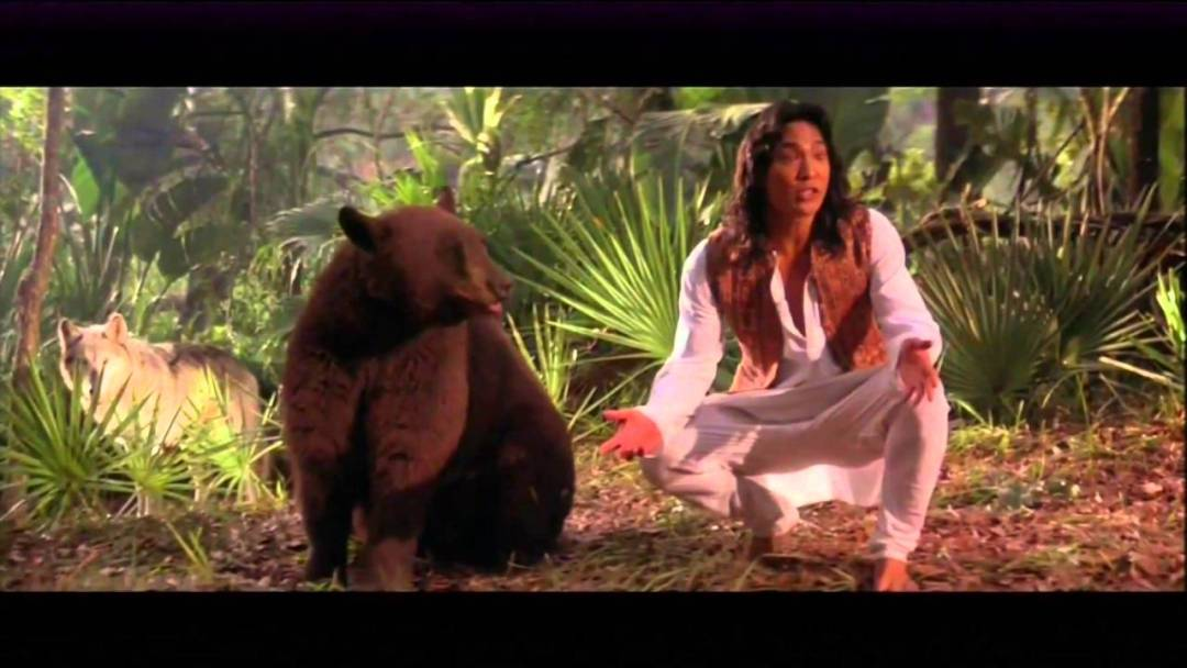 A still from the 1994 movie of Jason Scott Lee as Mowgli and the real bear used to play Baloo