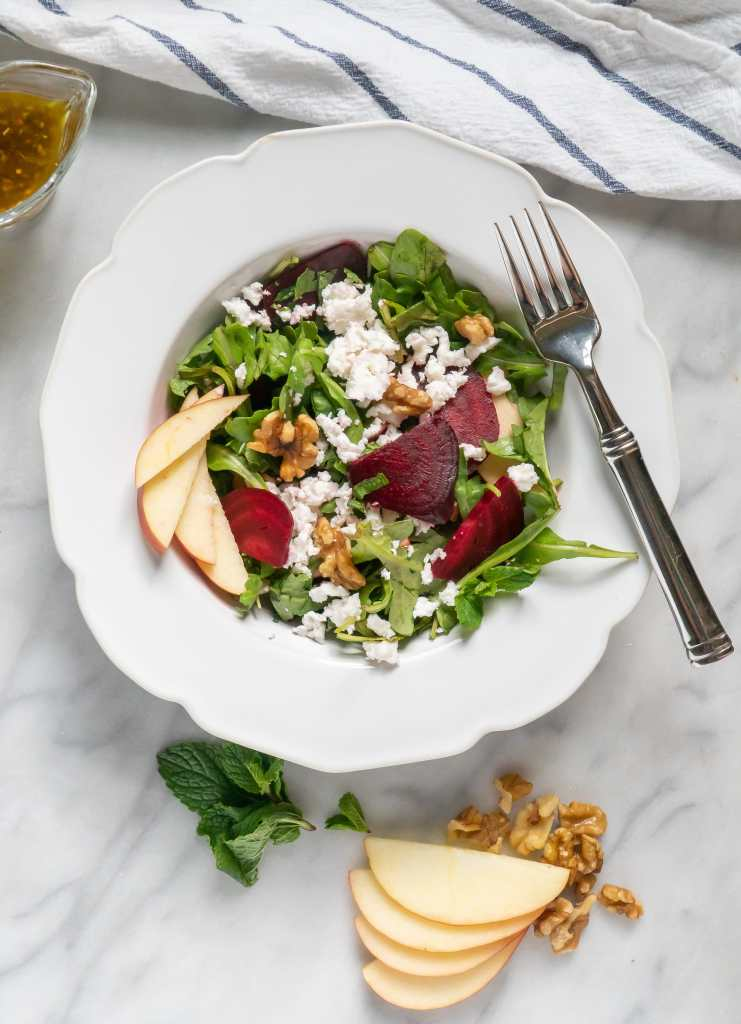 Roasted Beet Salad in white bowl with sliced apples