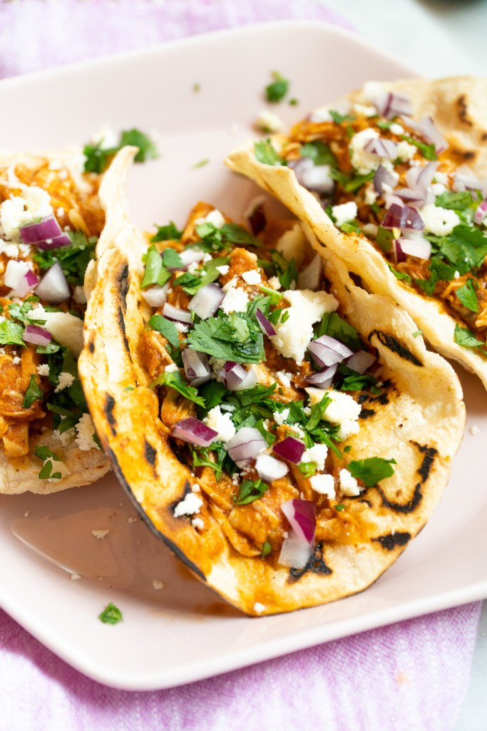 Up close photo of Chicken Tinga Tacos sprinkled with cilantro, red onion, and goat cheese