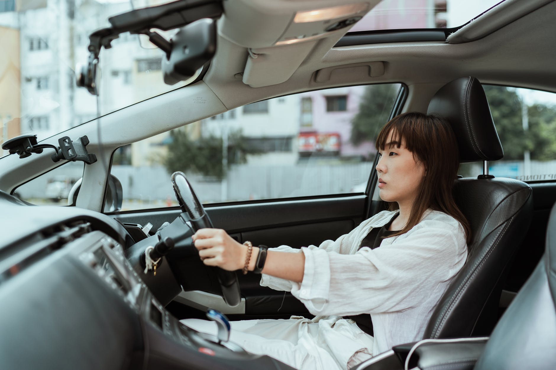 serious asian woman driving right hand car