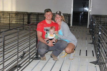 This is me, Scott (husband) and our son Will. This picture was taken after the construction of our hog barn was completed. We were setting up & getting ready for baby pigs. Everyone has to pitch in and help-even Will!