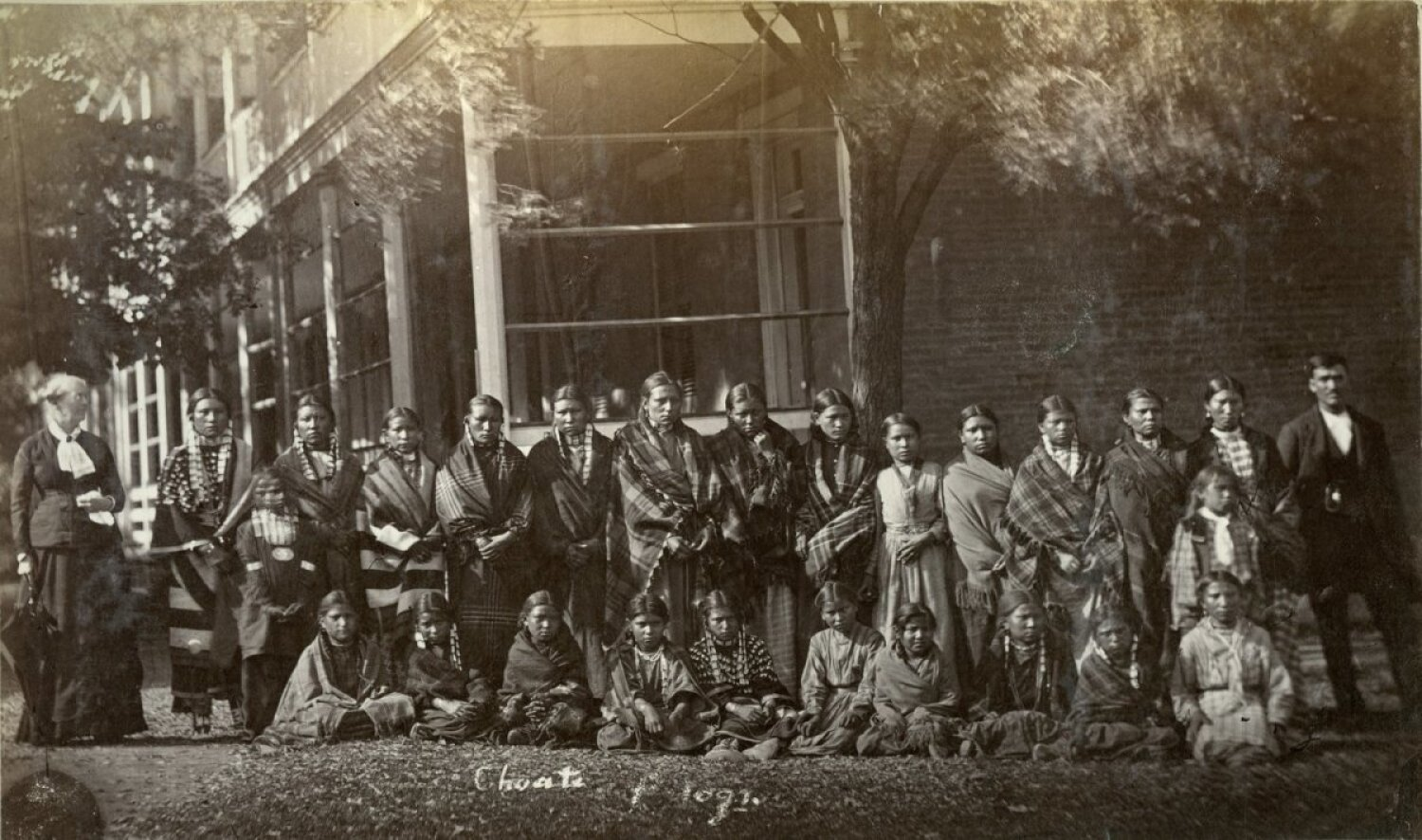 A group portrait shows the first female students to arrive at the Carlisle Indian Industrial School from the Pine Ridge and Rosebud Sioux reservations on October 6, 1879. Several of the girls in the photo later died and were buried at the school for more than 140 years before finally being sent to their relatives in South Dakota in July 2021. School matron Sarah Mather is standing at left and interpreter Charles Tackett is standing at right. (Photo courtesy of the Cumberland County Historical Society)