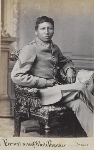 A studio portrait from about 1880 shows Ernest (Knocks Off), Sicangu Oyate, wearing a Carlisle Indian Industrial School uniform. Ernest arrived at the school in the first group of students from Pine Ridge and Rosebud on Oct. 6, 1879, and died on Dec. 13, 1880. His remains were finally shipped home to his family 140 years later in July 2021. (Photo courtesy of the Cumberland County Historical Society)