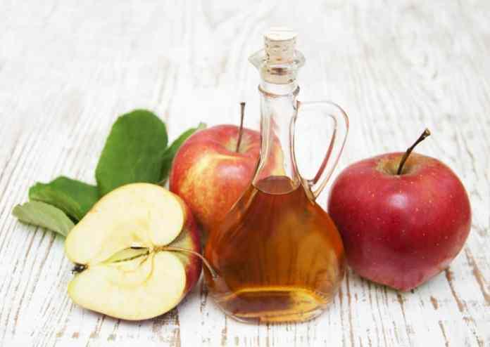 Apple cider vinegar and fresh apple on a wooden background